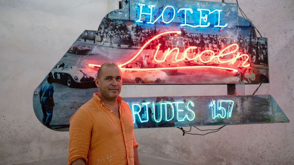 Artist Kadir López in front of one of the many neon signs he's restored on display in the REX (Credit: Claire Boobbyer)