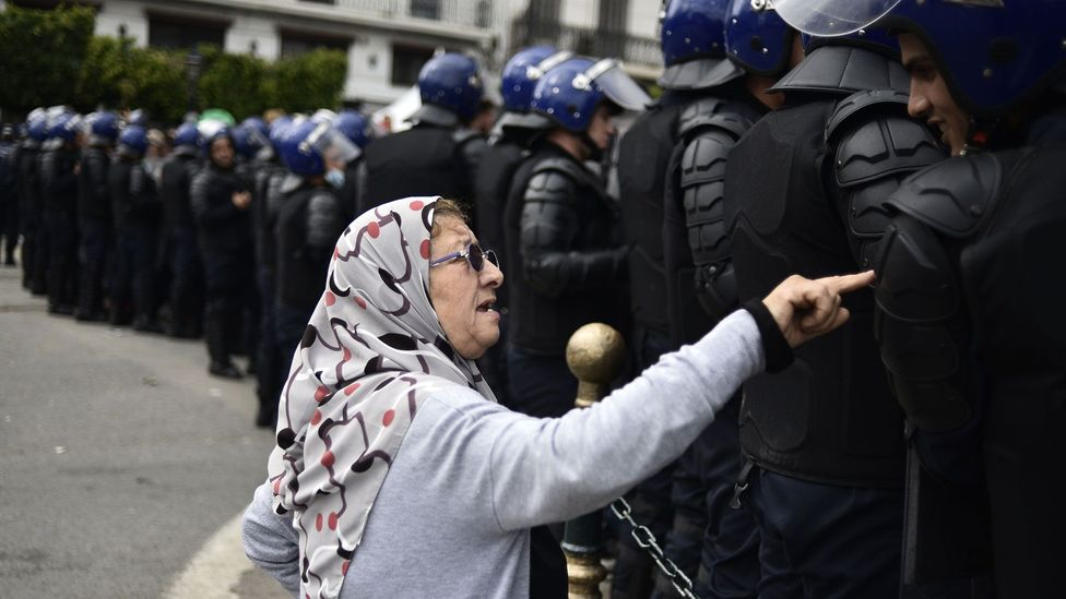An elderly woman talks to the Algerian security forces during the recent protests (Credit: Getty Images)