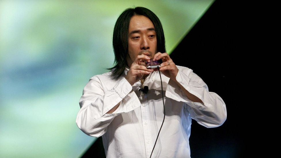 Ge Wang, co-founder of the software start-up Smule, turns an iPhone into an instrument called an ocarina and plays music on it (Credit: Getty Images)