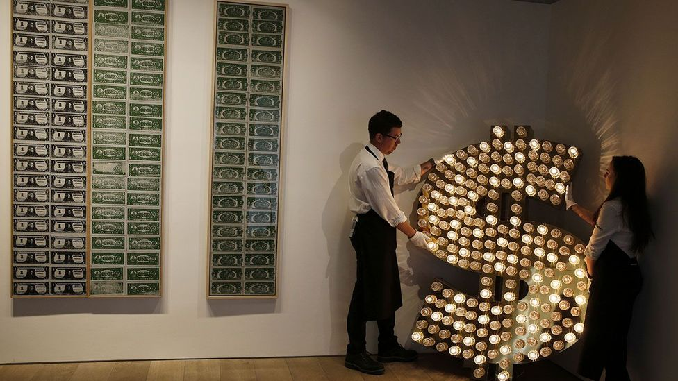 Artwork made from reflector caps, lamps and an electronic sequencer, by artists Tim Noble and Sue Webster alongside pieces by Andy Warhol (Credit: Getty Images)