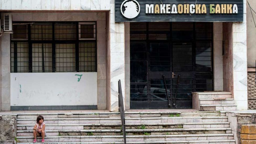 A young girl sits outside a bank in Veles (Credit: Getty Images)