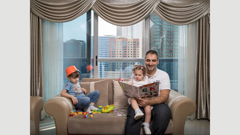 Fouad Kuyali reads to his children Mazen and Julie in their home in Dubai, where he moved from Aleppo, Syria (Credit: Gabriele Galimberti/INSTITUTE)