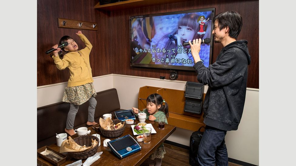 Takeshi Masuma works 40-hour weeks as an accountant in Tokyo. In his little spare time with his daughters, he likes to take them to karaoke (Credit: Gabriele Galimberti/INSTITUTE)