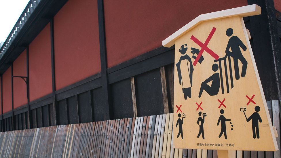 A language-free placard in Kyoto, Japan with directions that aim to curb problematic tourist behaviour (Credit: Getty Images)