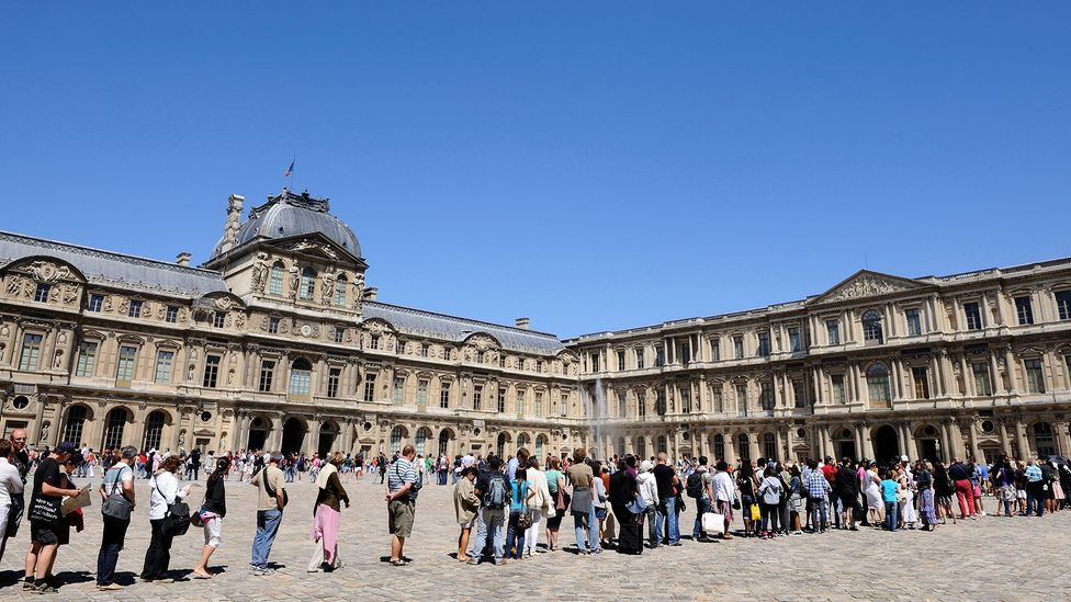 Tourists queue in front of the Louvre in Paris in 2017. The museum shut down for one day earlier this year after employees walked out due to overcrowding (Credit: Getty Images)