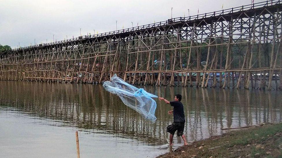 A man fishes near the Mon Bridge in Sangkhlaburi, Thailand