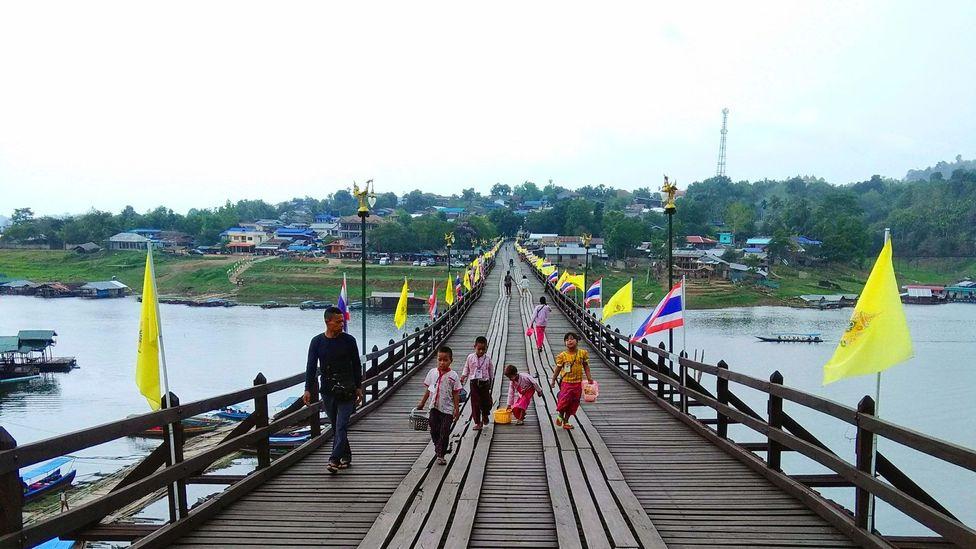 People walk across the Mon Bridge in Sangkhlaburi, Thailand