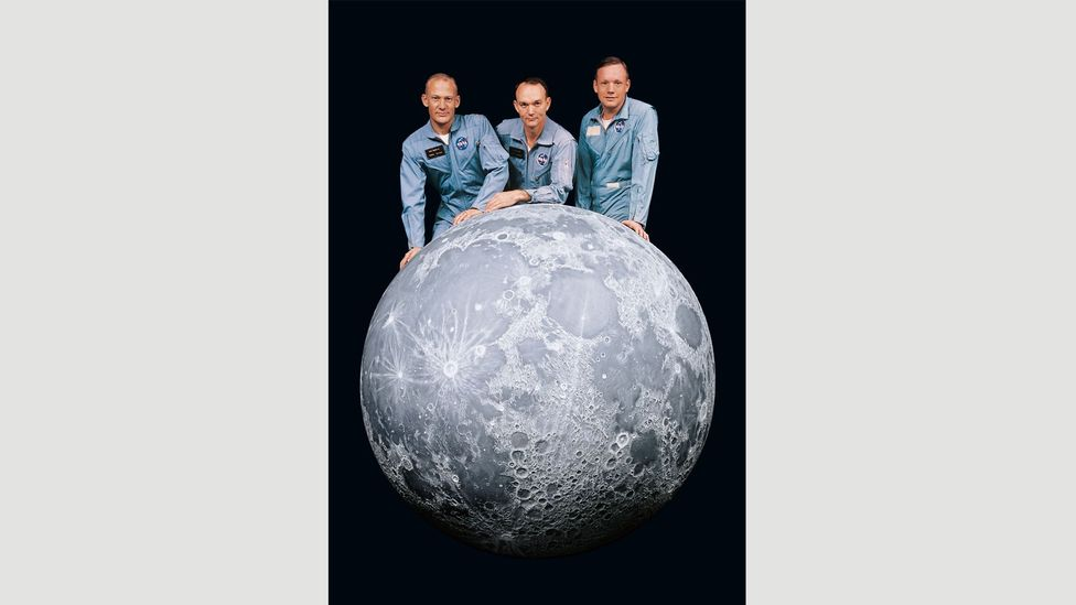 Left to right: Aldrin, Collins and Armstrong on 13 April, 1969, next to a model of the Moon mapping every major crater and mountain known to date