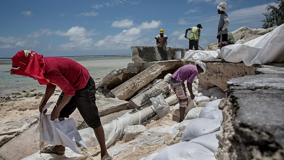 Locals regularly have to repair roads damaged by flooding on the islands in the Republic of Kiribati (Credit: Getty Images)