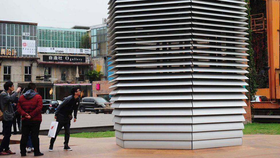 Residents inspect the 'smog free tower' – a 7m-high (23ft) filter hoped to help clean up Beijing's atmosphere (Credit: Getty Images)