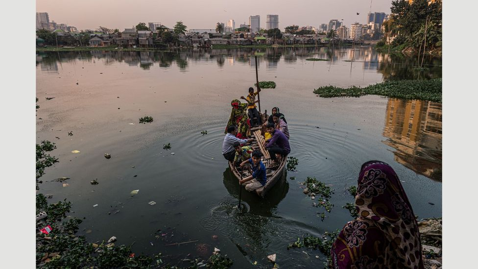 A family navigate the heavily flooded land around their slum, Korail, in Dhaka, the capital city of Bangladesh (Credit: Ignacio Marin/ Institute)