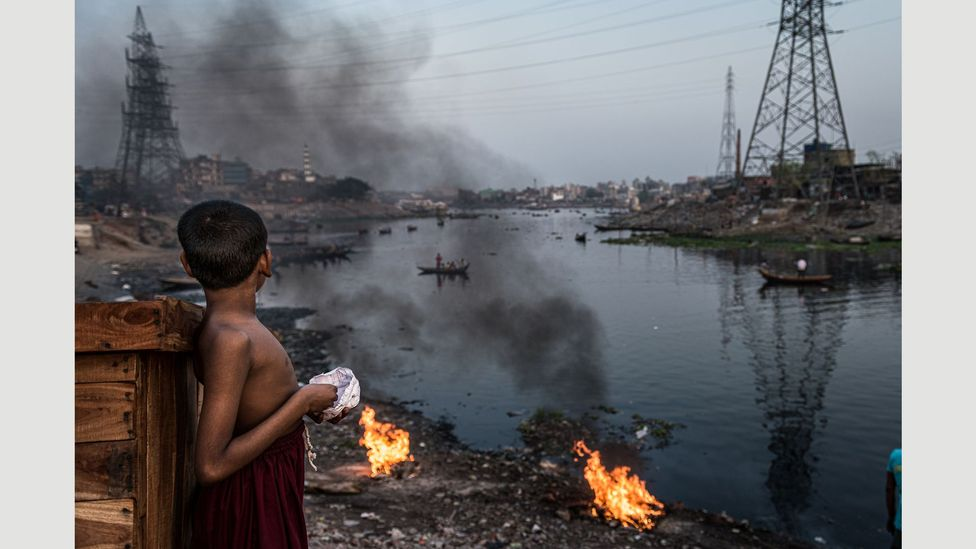 A child looks over the polluted Buriganga river that flows through slums in southwest Dhaka (Credit: Ignacio Marin/ Institute)