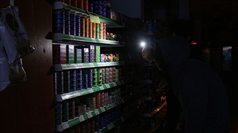 People use phones to illuminate goods in a supermarket in Buenos Aires, Argentina during a power cut (Credit: Getty Images)