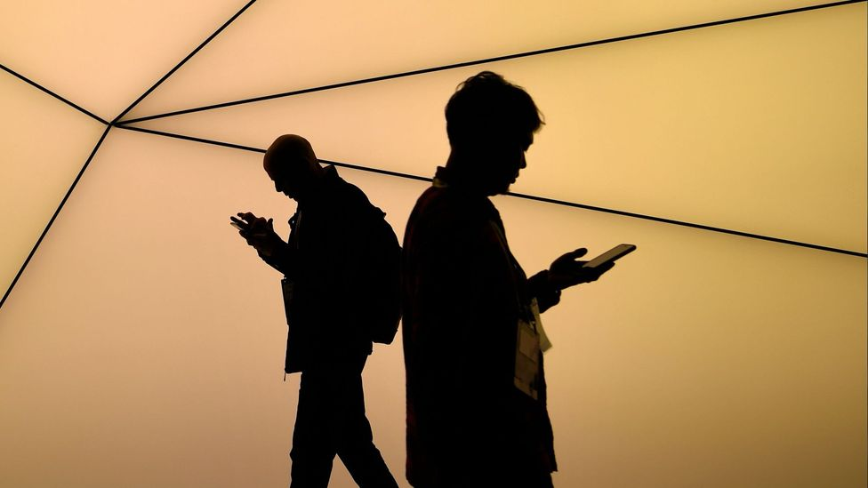 Silhouettes of two men using their smart phones