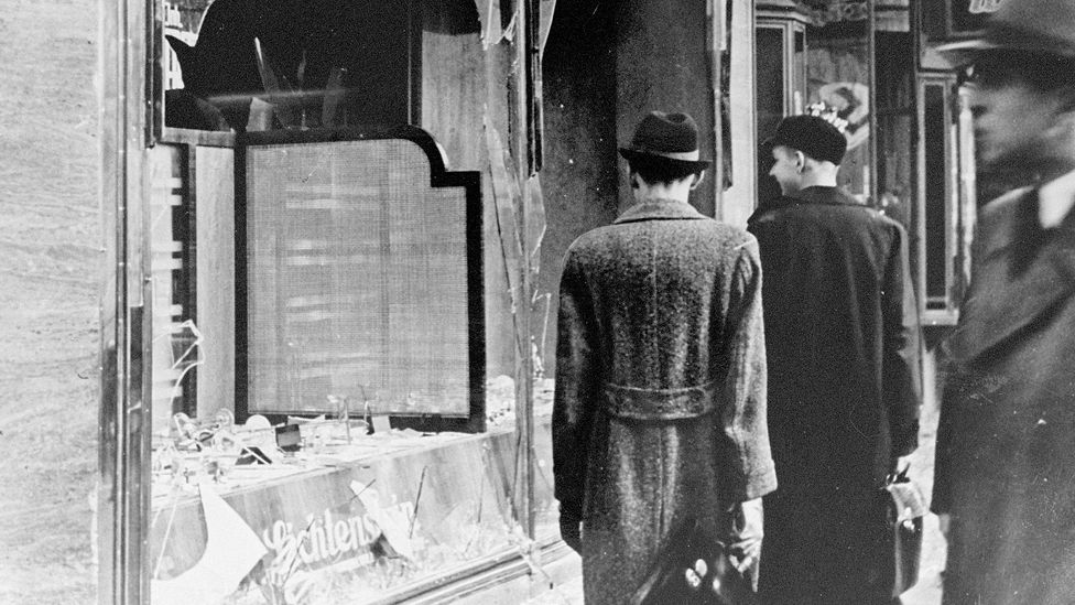 Germans pass by the broken windows of a shop in the aftermath of Kristallnacht, a night which showed the world how dangerous Germany was becoming for Jews (Credit: Getty Images)