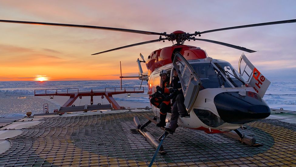 Expedition members sit in a BK-117 helicopter on board Polarstern, while a long-range Russian Mil Mi-8 flies in the background (Credit: AWI/Markus Rex)