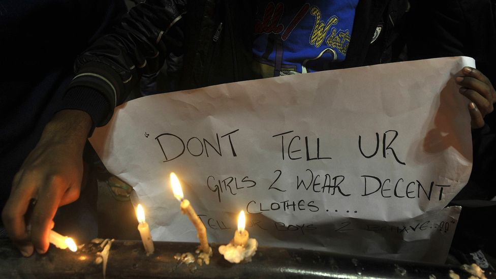 """""""Don't tell your girls to wear decent clothes – tell your boys to behave,"""" reads a sign at a vigil for the victim of a brutal 2012 gangrape in New Delhi (Credit: Getty Images)"""