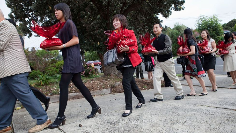 A queue of guests arriving with gifts at a bride's house on the morning of a Chinese wedding (Credit: Alamy)
