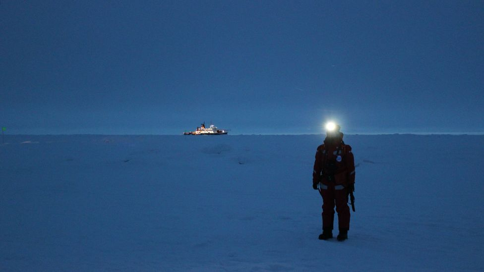 An expedition member waits for a helicopter to arrive on the sea ice near Polarstern (Credit: Martha Henriques)