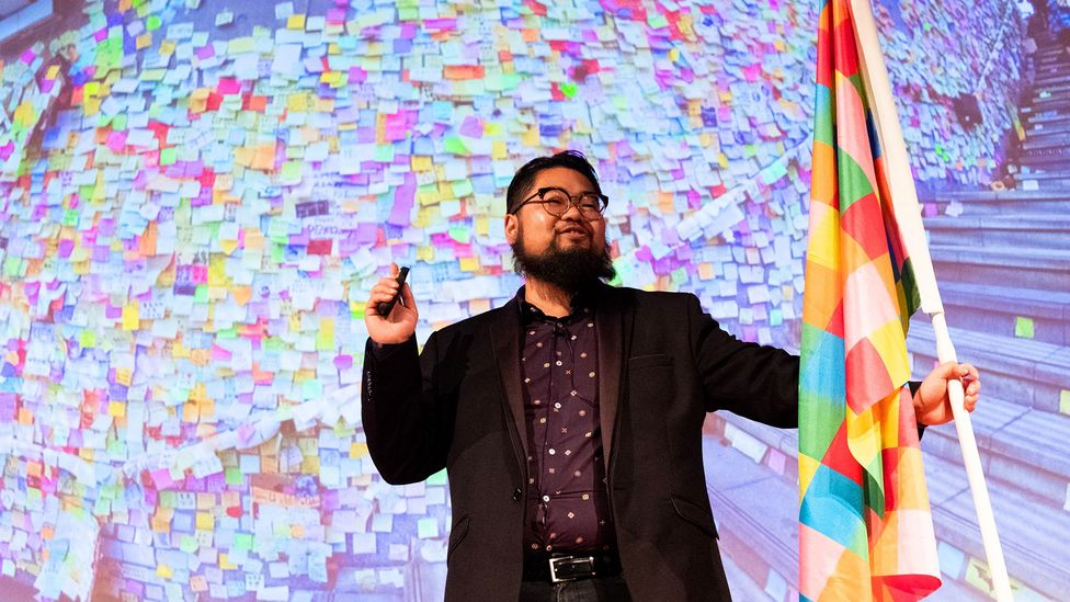 Political cartoonist Badiucao holds the flag that was inspired by the Lennon walls around the city (Credit: Getty Images)