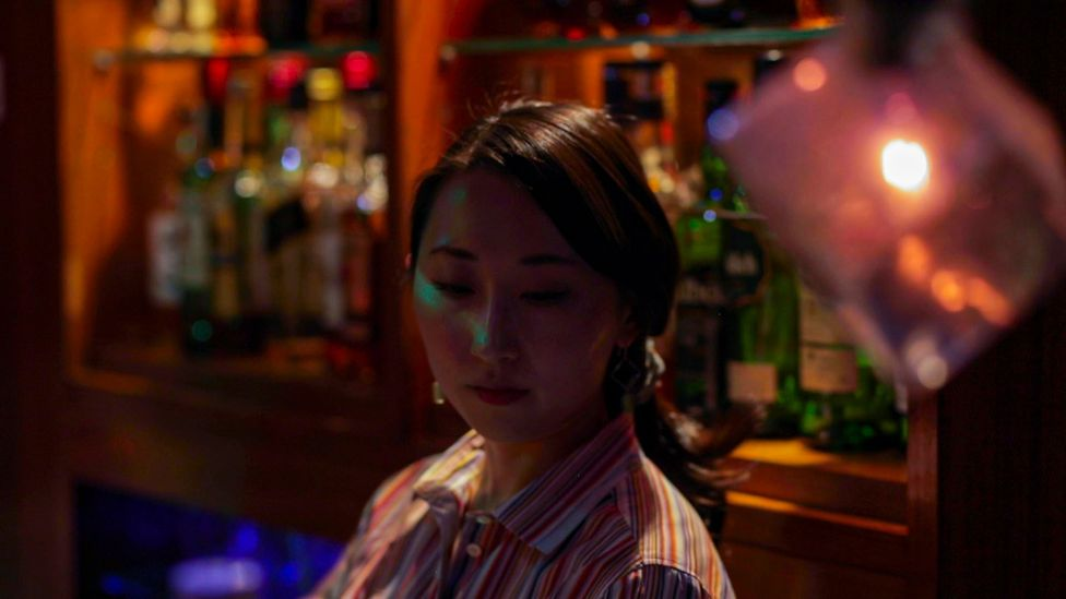 """Miki Tateishi is a bartender at Hitori, a bar aimed at solo drinkers. A former customer herself, she thinks """"the world is changing"""" (Credit: Shiho Fukada and Keith Bedford)"""