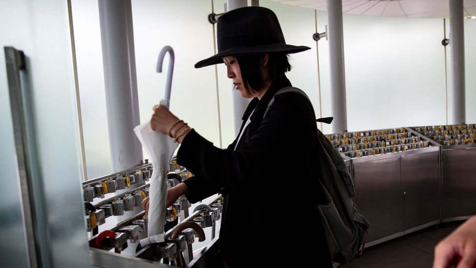 A Japanese woman keeps her umbrella under lock and key in Tokyo's National Art Center (Credit: Getty Images)