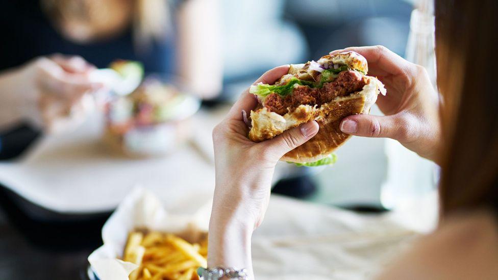 Woman eating vegan burger (Credit: Getty Images)