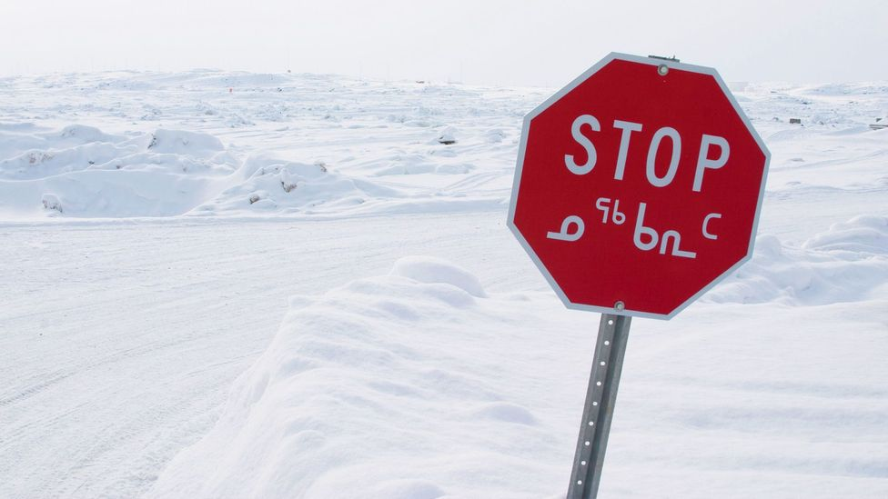 When they were educated using the Inuktitut alphabet, shown on a stop sign in Nunavut here, Inuit children were ahead of their peers taught in English or French (Credit: Alamy)