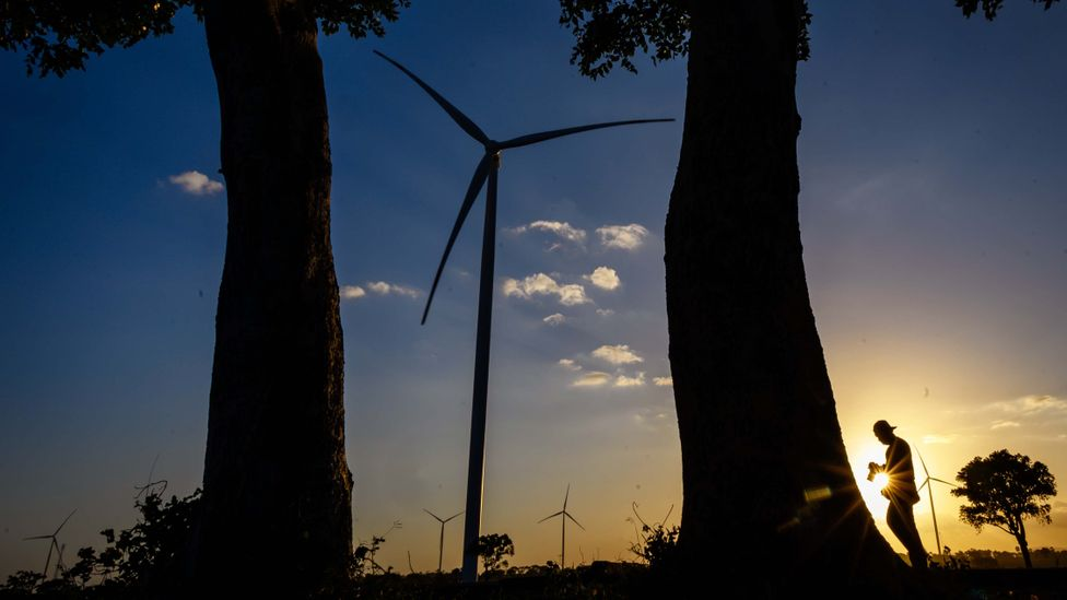 A man walks past wind turbines in Indonesia at dusk (Credit: Getty Images)