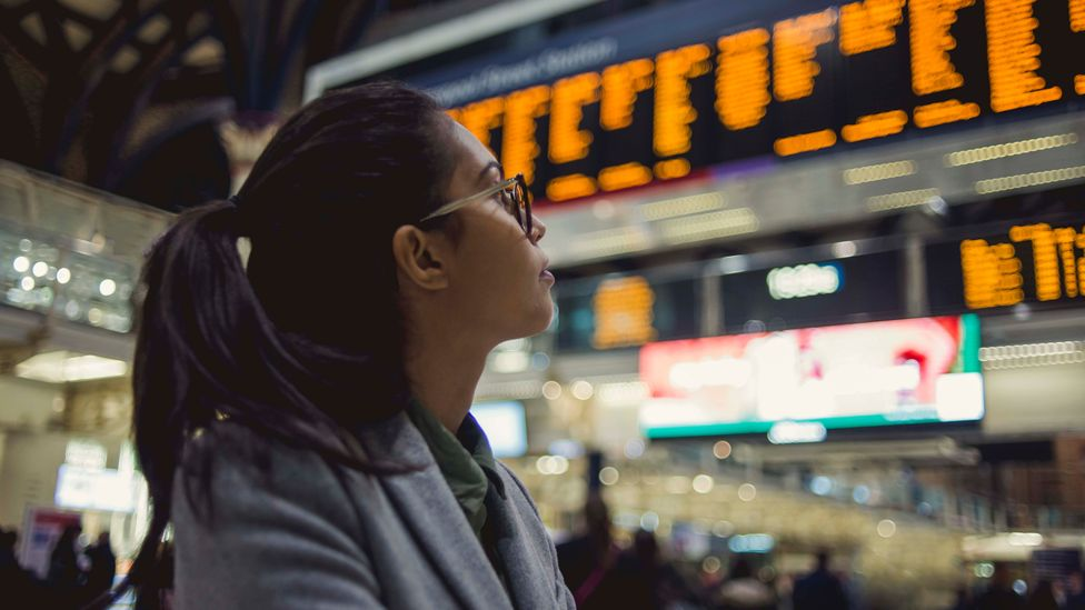 A woman looks at the train times displayed on screens in a station (Credit: Getty Images)