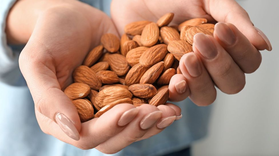 Woman with handful of almonds (Credit: Getty Images)