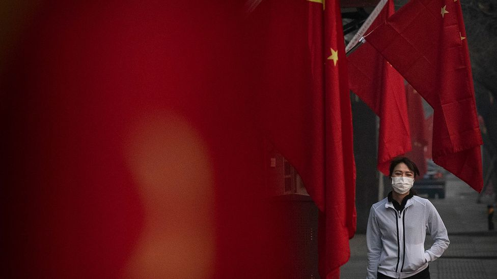 A young woman wearing a mask walks past Chinese flags (Credit: Getty Images)