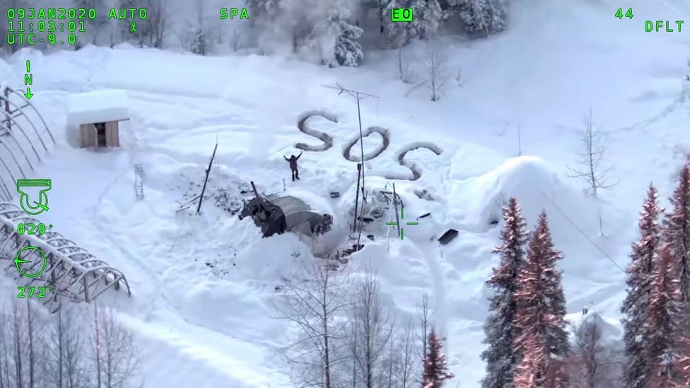Tyson Steele waves to the circling State Trooper helicopter surrounded by the debris of his hut (Credit: Alaska State Troopers)