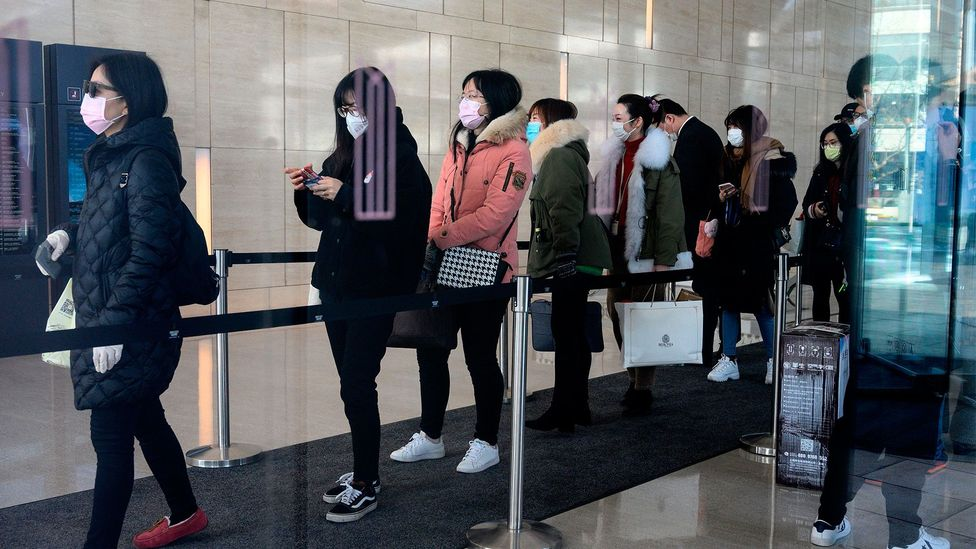 Workers queue to enter a Shanghai office on February 10 after an extended holiday  to slow the spread of the virus. Now, many such employees work remotely (Credit: Getty Images)
