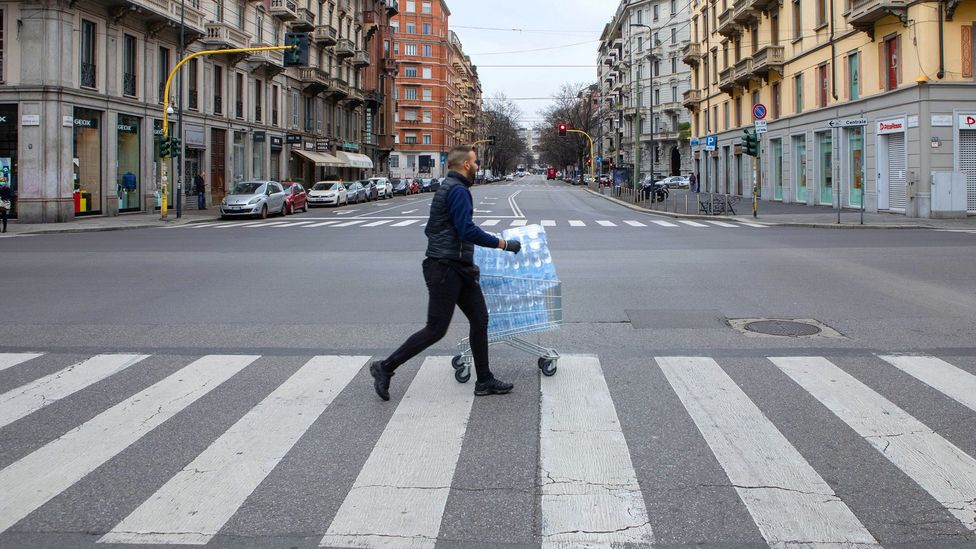 Man crossing the road with water bottles in a shopping trolly (Credit: Getty Images)
