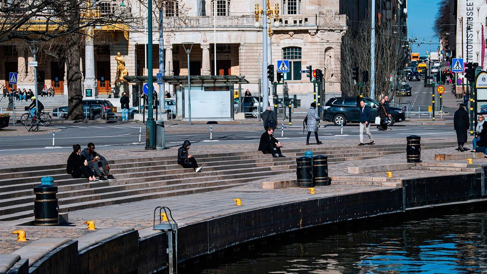People sit in the sun in Stockholm on March 26 during the Covid-19 pandemic (Credit: Getty Images)
