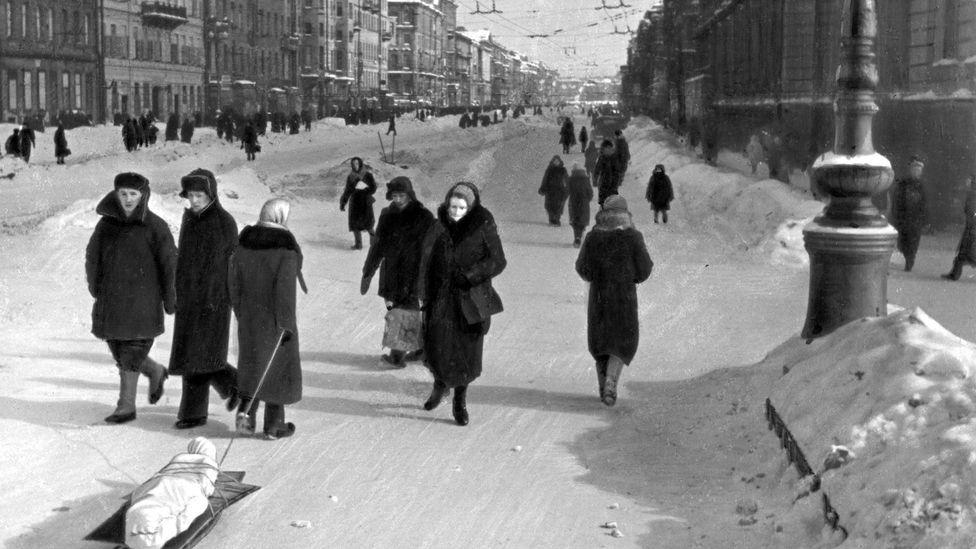 Residents walk through the streets of besieged Leningrad. One pulls the body of a dead relative on a sled (Credit: Getty Images)