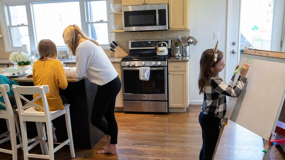 Farrah Eaton, former high school administrator, assists her children with home-schooling in New York. (Credit: Getty Images)