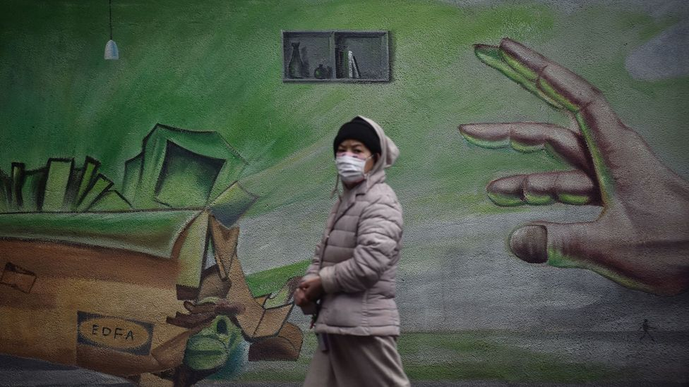 Woman in mask walking past hand graffiti (Credit: Getty Images)