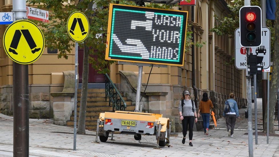 A digital sign asking people to wash their hands (Credit: Getty Images)