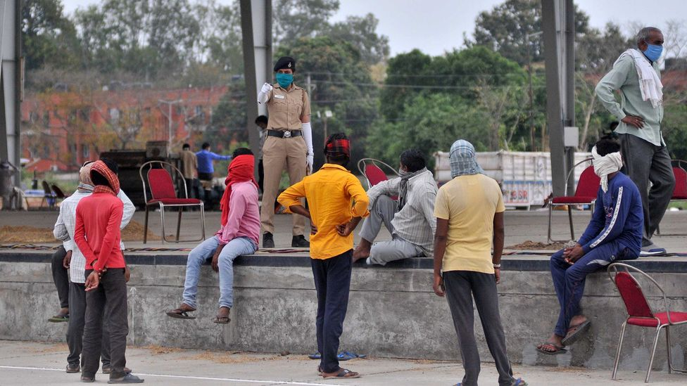 A police official warns labourers to wear face masks at the grain market in Chandigarh, India (Credit: Getty Images)