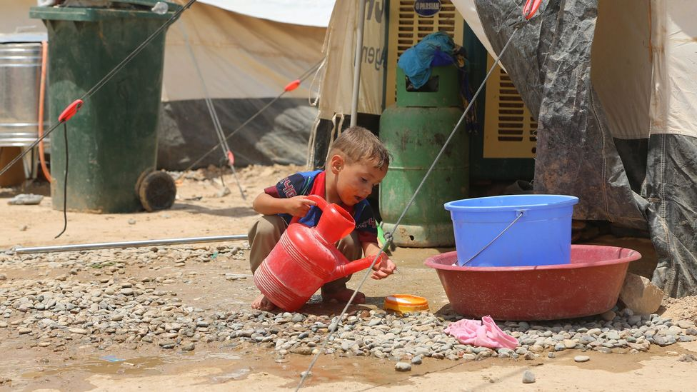 A boy washes at the Dibege Refugee Camp in Iraq; ensuring that there are handwashing stands and soap is key to fighting Covid-19's spread in refugee camps (Credit: Getty Images)