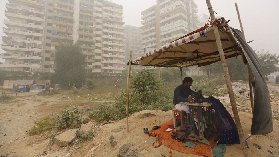 A roadside tailor stitches cloths in heavy smog in New Delhi, India; air pollution is linked to weakened respiratory health (Credit: Getty Images)