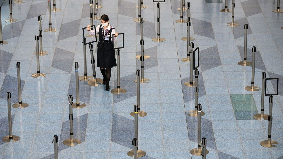 Tokyo's Haneda Airport in March as the coronavirus spread across the globe. Though much emptier, social distancing is in full effect at airports (Credit: Getty Images)