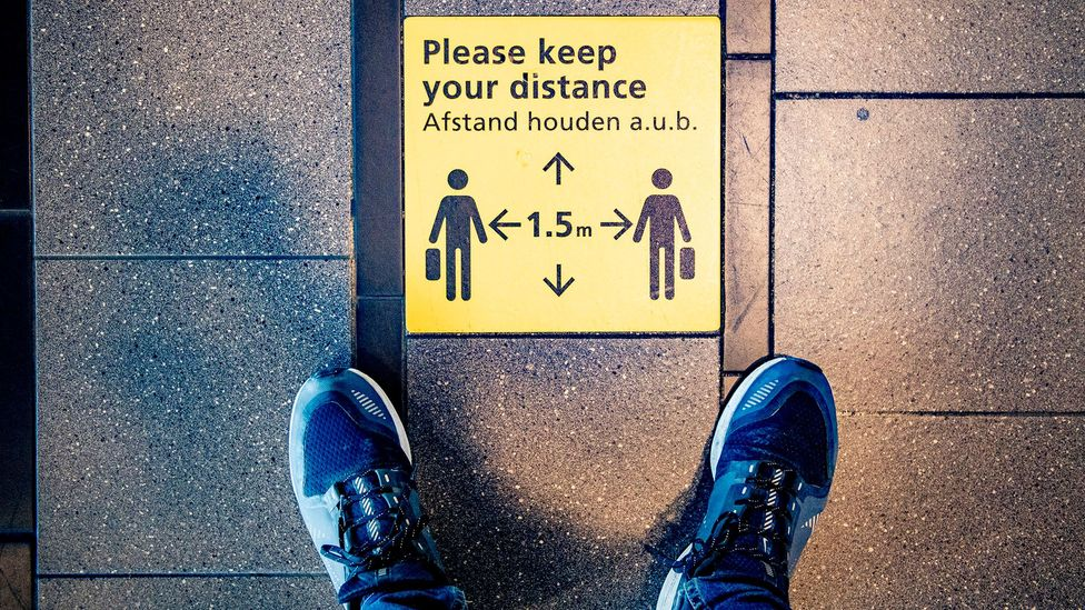 Airports have installed signs urging social distance, like at Schiphol airport in the Netherlands (Credit: Getty Images)