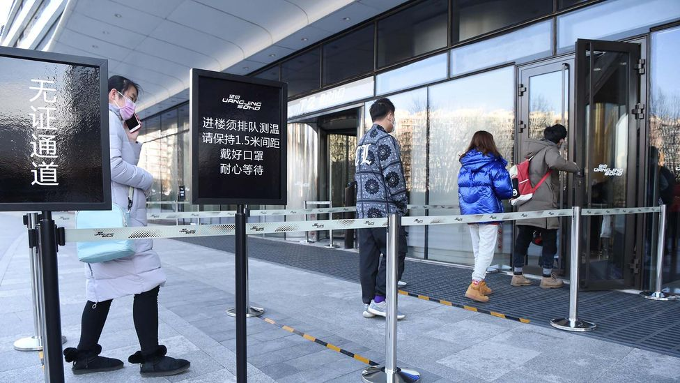 People wait in a queue to have their temperature and identity information checked at an entrance to office in Beijing, China (Getty Images)
