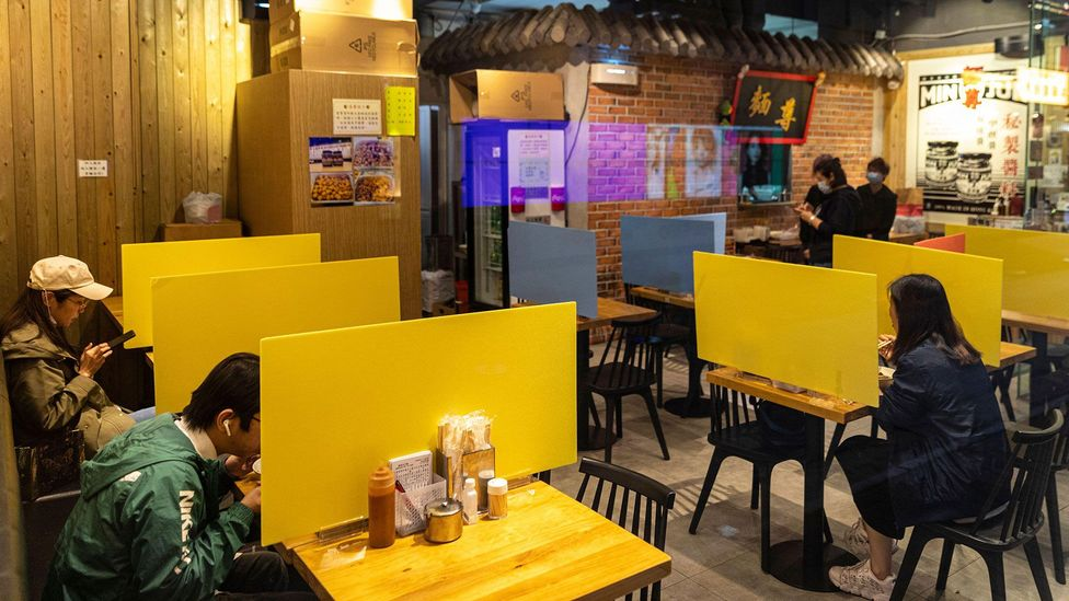 Plastic barriers like these, at a restaurant in Hong Kong in April 2020, are based on 'defensive design' principles (Credit: Alamy)