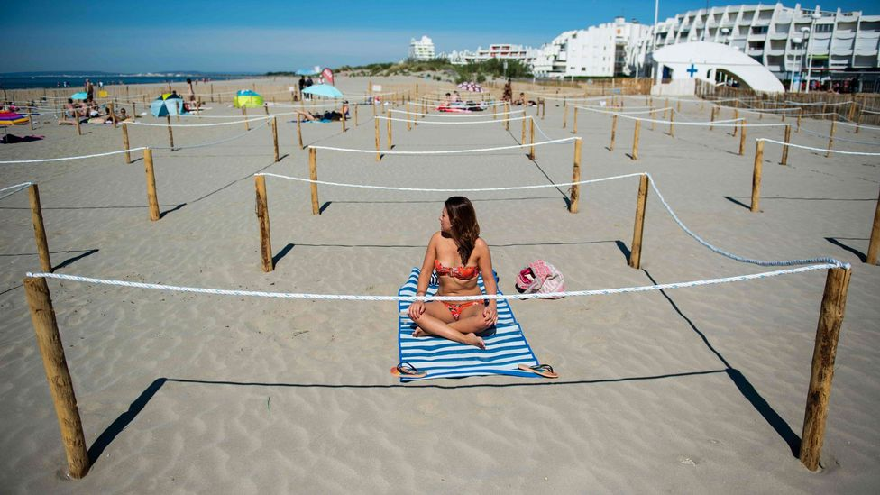 A woman in a bikini sits on the beach (Credit: Getty Images)