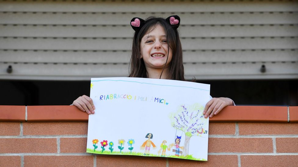 A girl on a balcony poses with a picture she drew (Credit: Reuters)