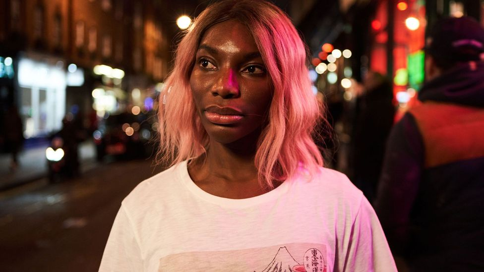 Michaela Coel as Arabella in I May Destroy You. Arabella, who has short pink hair, stands alone on a street at night, illuminated by the bright lights. She looks pensively into the distance.